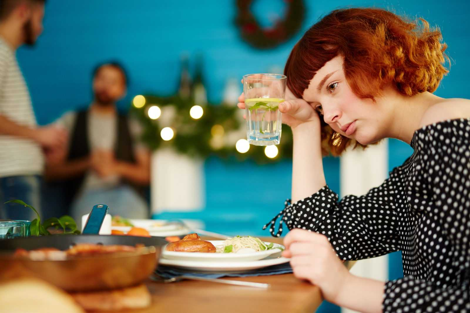 Women during family holiday dinner looking sad